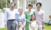 庭で微笑む親子3世代
