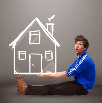 Attractive young boy holding a huge drawn house